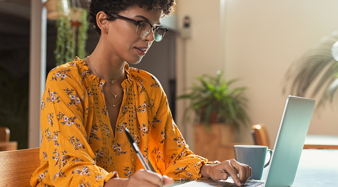 Woman in yellow blouse and glasses taking notes with pen and paper while looking at laptop computer
