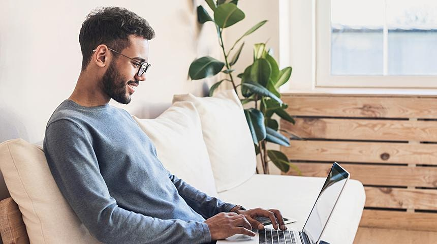 Person sitting on couch smiling and working on laptop.