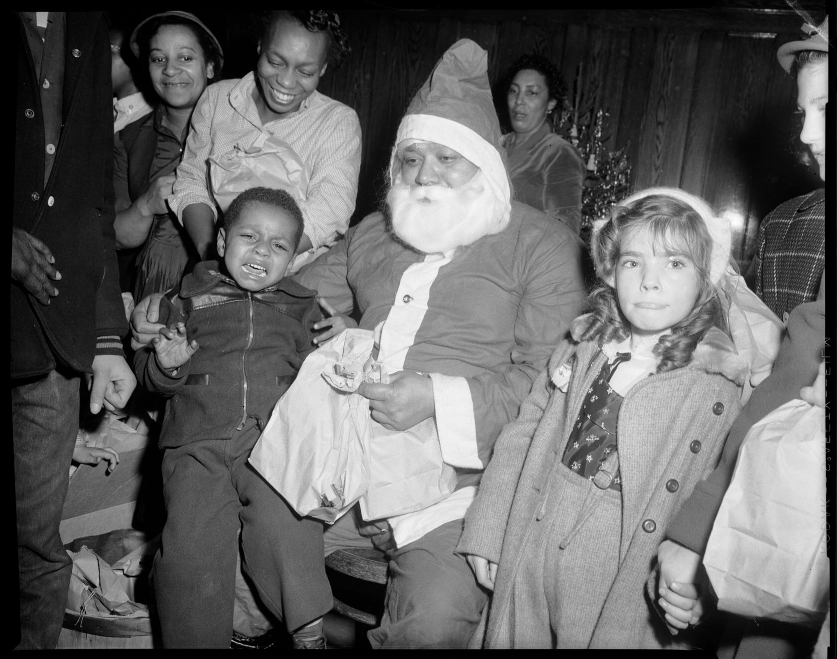 Child sits and cries on a fake Santa Claus's lap at the East Liberty library branch circa 1955.