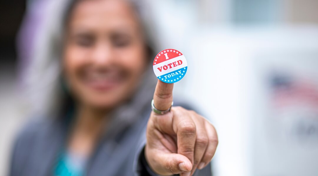 """Woman with gray hair holding an """"I Voted Today"""" sticker up to the camera"""