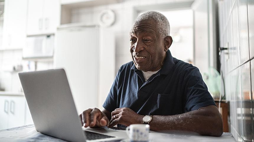 Person sitting in their kitchen working on a laptop.
